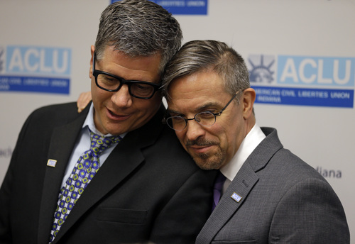 Rob MacPherson, right, and his husband Steven Stolen, hug during a news conference at the ACLU in Indianapolis, Monday, Oct. 6, 2014. The U.S. Supreme Court on Monday turned away appeals from Indiana and four other states seeking to prohibit same-sex marriages, paving the way for an immediate expansion of gay and lesbian unions. (AP Photo/Michael Conroy)