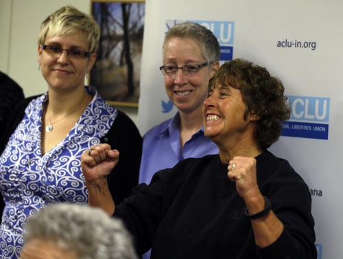 Teresa Welborn, right, cheers at an ACLU news conference in Indianapolis, Monday, Oct. 6, 2014, after it was announced that the U.S. Supreme Court turned away appeals from Indiana and four other states seeking to prohibit same-sex marriages, paving the way for an immediate expansion of gay and lesbian unions. Welborn, one of the litigants in the case, is joined by fellow litigates Melady Betterman-Layne, left, and her partner Tarra Betterman-Layne. (AP Photo/Michael Conroy)