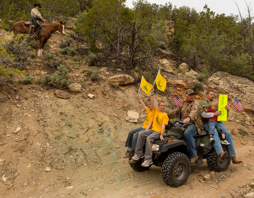 Trent Nelson  |  The Salt Lake Tribune Under the eyes of a mounted Kane County Sheriff's Deputy, ATV riders make their way into Recapture Canyon, which has been closed to motorized use since 2007. The protest on Saturday, May 10, 2014, north of Blanding, came after a call-to-action by San Juan County Commissioner Phil Lyman.