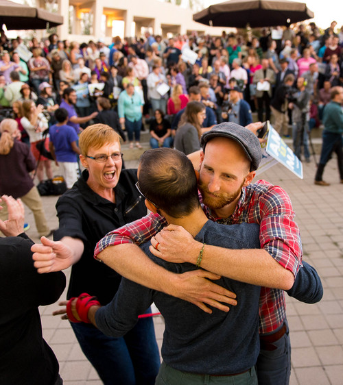 Trent Nelson  |  The Salt Lake Tribune Debbie Johnson rushes in to embrace Kitchen v. Herbert plaintiffs Derek Kitchen and Moudi Sbeity at a rally to celebrate today's legalization of same-sex marriage, Monday October 6, 2014 in Salt Lake City.