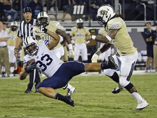 Brigham Young running back Paul Lasike (33) is brought down by Central Florida defensive back Clayton Geathers (26) after a reception in the first half of an NCAA college football game in Orlando, Fla., Thursday, Oct. 9, 2014. (AP Photo/John Raoux)