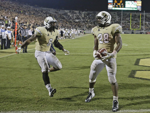 Central Florida wide receiver Rannell Hall (6) runs to congratulate running back William Stanback (28) on scoring the winning touchdown in overtime to defeat Brigham Young in an NCAA college football game in Orlando, Fla., Thursday, Oct. 9, 2014. Central Florida won 31-24 in overtime. (AP Photo/John Raoux)