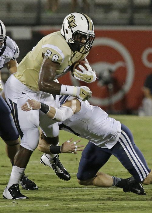 Central Florida running back William Stanback, left, is stopped by Brigham Young defensive back Skye PoVey after a short gain during the first half of an NCAA college football game in Orlando, Fla., Thursday, Oct. 9, 2014. (AP Photo/John Raoux)