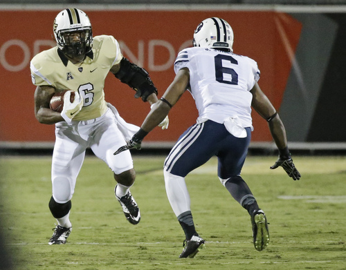 Central Florida wide receiver Rannell Hall, left, runs with the ball as Brigham Young defensive back Jordan Johnson tries to stop him during the first half of an NCAA college football game in Orlando, Fla., Thursday, Oct. 9, 2014. (AP Photo/John Raoux)
