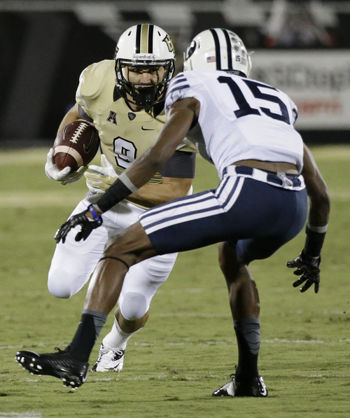 Central Florida wide receiver J.J. Worton, left, looks for a way around Brigham Young defensive back Michael Davis (15) after a reception during the first half of an NCAA college football game in Orlando, Fla., Thursday, Oct. 9, 2014. (AP Photo/John Raoux)