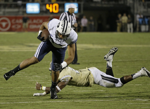 Brigham Young tight end Devin Mahina, left, slips past Central Florida defensive back Clayton Geathers, right, for a 15-yard touchdown during the second half of an NCAA college football game in Orlando, Fla., Thursday, Oct. 9, 2014. Central Florida won 31-24 in overtime. (AP Photo/John Raoux)