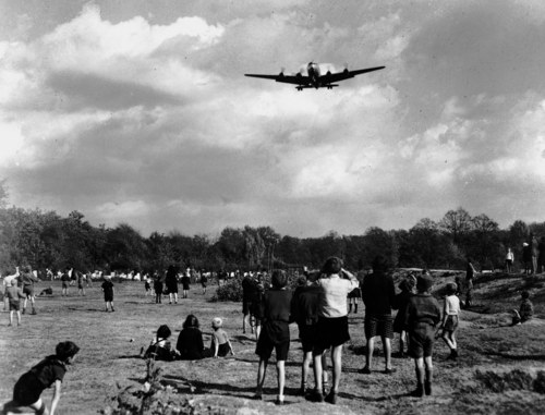 An Oct. 4, 1948 file photo shows Berlin children gazing hopefully at the sky, waiting for candy bars to be dropped from an airlift  C-54 Skymaster passing overhead on its approach to Tempelhof Airport.. This is the exact spot where Lt. Gail Halvorsen dropped candy to the youngsters by way of handkerchief parachutes on each on his trips to Berlin.  (AP Photo/File)