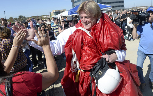 """Al Hartmann     The Salt Lake Tribune Overstock.com CEO Patrick Byrne (still wrapped in his parachute from a drop of 18,000 feet) high fives employees for the company's ground breaking of a $100 million campus that it is calling the """"Peace Coliseum,"""" which will cover 230,793 square feet. It will look like a peace sign from overhead and the Roman Colosseum from the ground.  The parcel is on the northwest corner of the property at 7200 S. 900 West"""