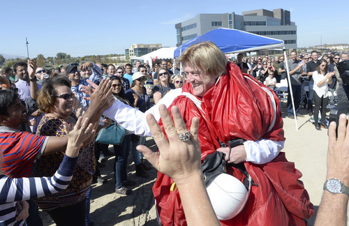 Al Hartmann     The Salt Lake Tribune Overstock.com CEO Patrick Byrne (still wrapped in his parachute from a drop of 18,000 feet) high fives employees for the company's ground breaking of a $100 million campus that it is calling the ìPeace Coliseum,î which will cover 230,793 square feet. It will look like a peace sign from overhead and the Roman Colosseum from the ground.  The parcel is on the northwest corner of the property at 7200 S. 900 West