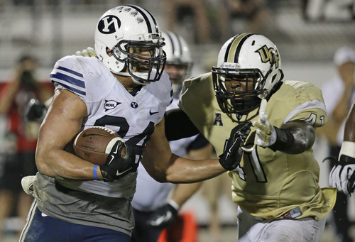 Brigham Young running back Algernon Brown, left, tries to get past Central Florida linebacker Terrance Plummer, right, during the second half of an NCAA college football game in Orlando, Fla., Thursday, Oct. 9, 2014. Central Florida won 31-24 in overtime. (AP Photo/John Raoux)