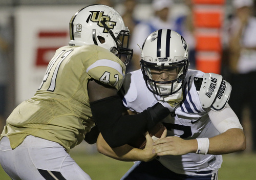 Central Florida linebacker Terrance Plummer (41) sacks Brigham Young quarterback Christian Stewart, right, during the second half of an NCAA college football game in Orlando, Fla., Thursday, Oct. 9, 2014. Central Florida won 31-24 in overtime. (AP Photo/John Raoux)