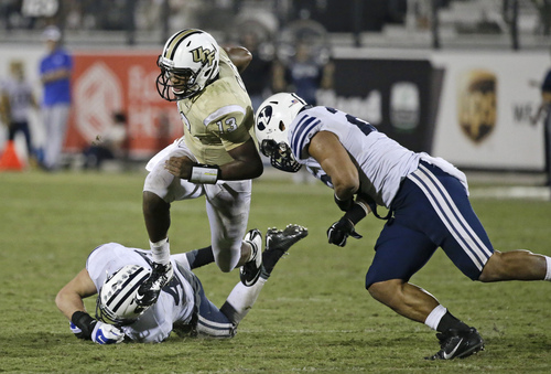 Central Florida quarterback Justin Holman (13) scrambles for yardage as he tries to get around Brigham Young linebacker Zac Stout, left, and Brigham Young defensive back Kai Nacua, right,  during the second half of an NCAA college football game in Orlando, Fla., Thursday, Oct. 9, 2014. Central Florida won 31-24 in overtime. (AP Photo/John Raoux)