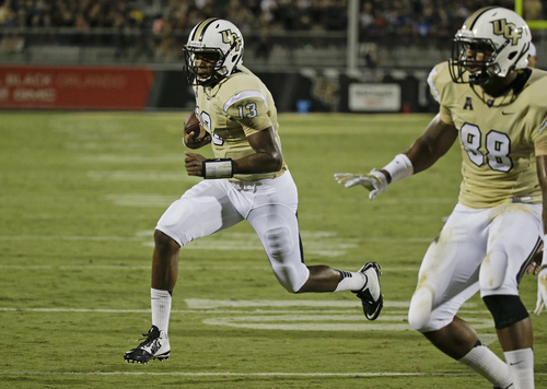 Central Florida quarterback Justin Holman (13) runs for a 5-yard touchdown against Brigham Young as teammate wide receiver Jordan Akins (88) runs interference during the first half of an NCAA college football game in Orlando, Fla., Thursday, Oct. 9, 2014. (AP Photo/John Raoux)