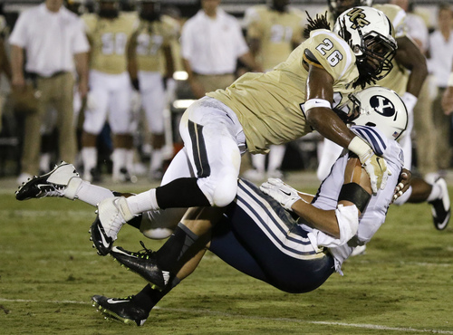 Central Florida defensive back Clayton Geathers (26) stops Brigham Young wide receiver Colby Pearson after a reception during the first half of an NCAA college football game in Orlando, Fla., Thursday, Oct. 9, 2014. (AP Photo/John Raoux)