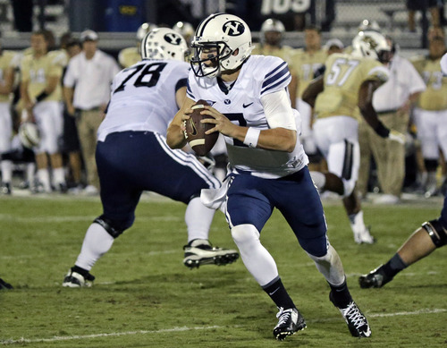 BYU quarterback Christian Stewart scrambles for yardage against Central Florida during the first half of an NCAA college football game in Orlando, Fla., Thursday, Oct. 9, 2014. (AP Photo/John Raoux)