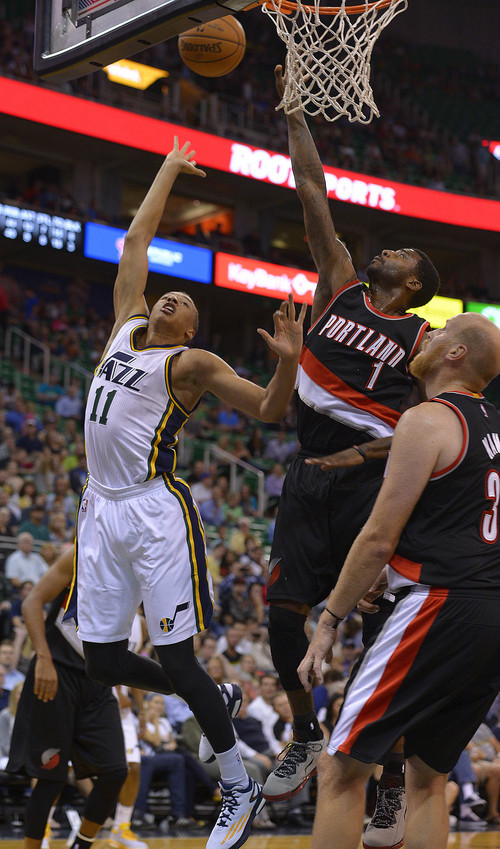 Leah Hogsten  |  The Salt Lake Tribune Utah Jazz guard Dante Exum (11) floats to the net over Portland Trail Blazers forward Dorell Wright (1). Utah Jazz defeated the Portland Blazers 92-73 during Tuesday's, October 7, 2014 preseason opener at Energy Solutions Arena.