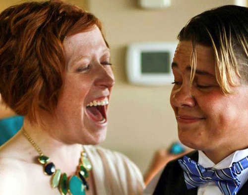 FILE - This undated handout file photo provided by Tracey Wiese, left, shows Wiese and Kat Cortez at a 2012 wedding for Cortez's sister. On Monday, May 12, 2014, they joined four other same-sex couples in suing the state of Alaska in federal court, arguing the state's constitutional ban on same-sex marriage violates their rights to due process and equal protection under the U.S. Constitution. On Sunday, Oct. 12, 2014, a federal judge struck down Alaska's first-in-the-nation ban on gay marriages. U.S. District Judge Timothy Burgess said the ban violates the U.S. constitutional guarantee of due process and equal protection.(AP Photo/Courtesy of Tracey Wiese, File)