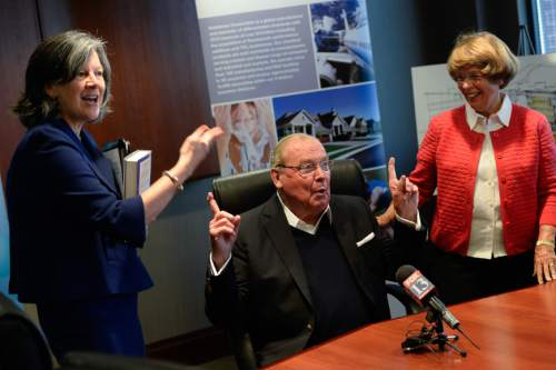 "Francisco Kjolseth  |  The Salt Lake Tribune Jon Huntsman Sr. expresses his gratitude for Mary Beckerle, CEO of Huntsman Cancer Institute, left, and his wife Karen during a press conference to announce the release of Huntsman's autobiography, ""Barefoot to Billionaire,"" followed by a book signing at Deseret Book in downtown Salt Lake City on Friday, Oct. 3. 2014."