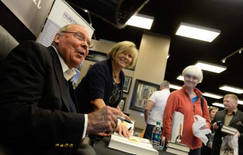 "Francisco Kjolseth  |  The Salt Lake Tribune Jon Huntsman Sr., signs copies of his new autobiography, ""Barefoot to Billionaire,"" at a book signing at Deseret Book in downtown Salt Lake City on Friday, Oct. 3. 2014."