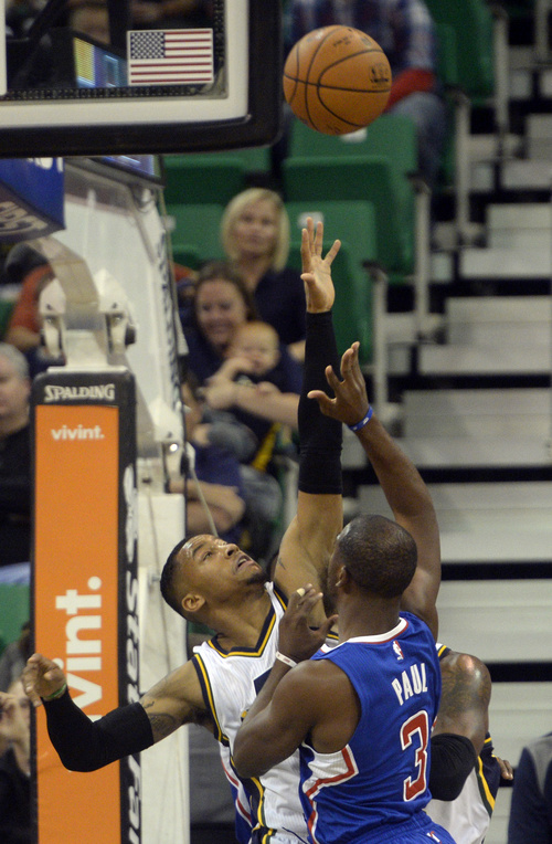 Rick Egan  |  The Salt Lake Tribune  Trey Burke (3) defends for the Jazz, as Los Angeles Clippers guard Chris Paul (3) takes a shot, in pre-season NBA action, Utah Jazz vs. The LA Clippers at EnergySolutions Arena, Monday, October 13, 2014