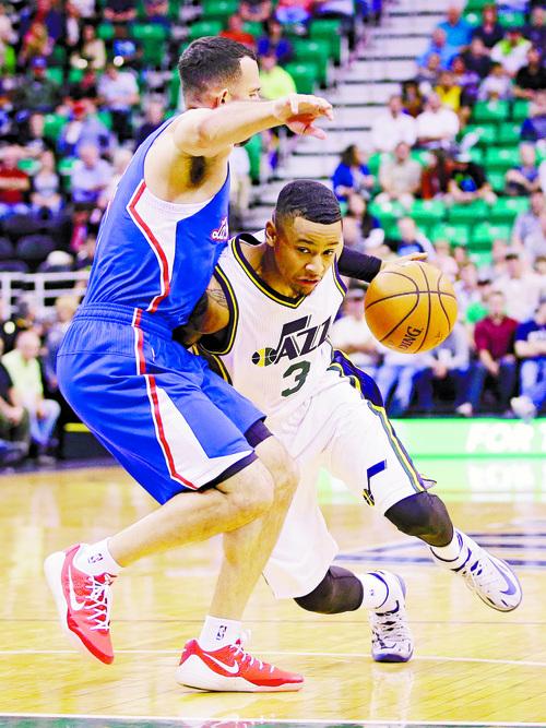 Utah Jazz's Trey Burke (3) drives around Los Angeles Clippers' Jordan Farmar, left, during the fourth quarter of an NBA pre-season basketball game Monday, Oct. 13, 2014, in Salt Lake City. The Jazz won 102-89. (AP Photo/Rick Bowmer) .