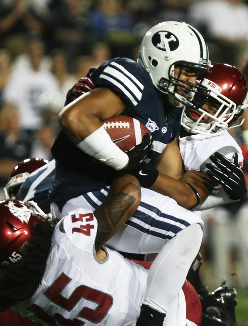 Kim Raff | The Salt Lake Tribune Brigham Young Cougars running back Iona Pritchard is brought down by Washington State Cougars (bottom) linebacker Chester Su'a and (top) Washington State Cougars safety Taylor Taliulu (30) during the BYU home opener at LaVell Edwards Stadium in Provo on Aug. 30, 2012.