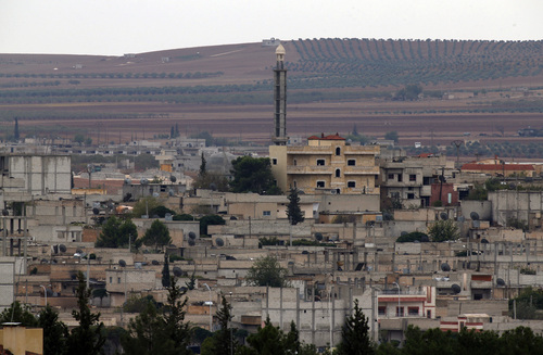 In this image shot from a hilltop in Mursitpinar on the outskirts of Suruc at the Turkey-Syria border, a partial view of Kobani, Syria, during fighting between Syrian Kurds and the militants of Islamic State group, Thursday, Oct. 16, 2014. Kobani, also known as Ayn Arab, and its surrounding areas, has been under assault by extremists of the Islamic State group since mid-September and is being defended by Kurdish fighters. (AP Photo/Lefteris Pitarakis)
