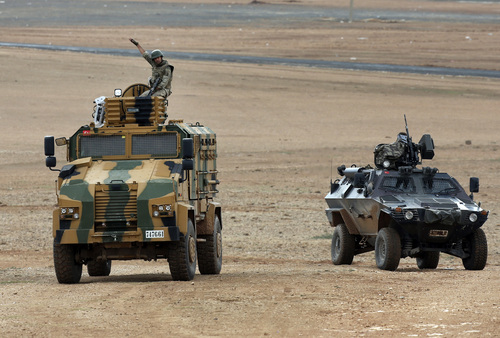 A Turkish forces soldier riding atop an armored vehicle gestures to members of the media to leave a hilltop overlooking Kobani, Syria, during fighting between Syrian Kurds and the militants of Islamic State group,  on the outskirts of Suruc, at the Turkey-Syria border, Thursday, Oct. 16, 2014. Kobani, also known as Ayn Arab, and its surrounding areas, has been under assault by extremists of the Islamic State group since mid-September and is being defended by Kurdish fighters. (AP Photo/Lefteris Pitarakis)