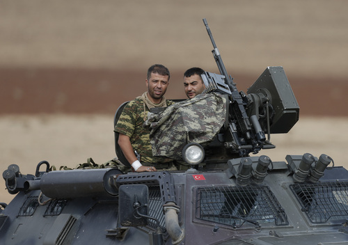 Turkish forces soldiers on their armoured vehicle patrol on the outskirts of Suruc, at the Turkey-Syria border, overlooking Kobani, Syria,during fighting between Syrian Kurds and the militants of Islamic State group, Thursday, Oct. 16, 2014. Kobani, also known as Ayn Arab, and its surrounding areas, has been under assault by extremists of the Islamic State group since mid-September and is being defended by Kurdish fighters. (AP Photo/Lefteris Pitarakis)