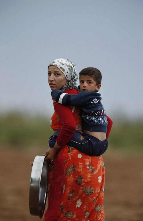 A Kurdish woman carries her child in Mursitpinar on the outskirts of Suruc, at the Turkey-Syria border, overlooking Kobani, Syria, during fighting between Syrian Kurds and the militants of Islamic State group, Thursday, Oct. 16, 2014. Kobani, also known as Ayn Arab, and its surrounding areas, has been under assault by extremists of the Islamic State group since mid-September and is being defended by Kurdish fighters. (AP Photo/Lefteris Pitarakis)
