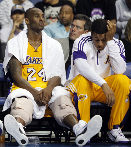 Los Angeles Lakers guard Kobe Bryant (24) and guard Jabari Brown, right, lament on the bench during the Golden State Warriors 116-75 win during the second half of a preseason NBA basketball game, Sunday, Oct. 12, 2014, in Ontario, Calif. (AP Photo/Alex Gallardo)