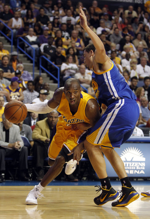 Los Angeles Lakers guard Kobe Bryant, left, drives to the basket against Golden State Warriors guard Klay Thompson during the first half of a preseason NBA basketball game, Sunday, Oct. 12, 2014, in Ontario, Calif. (AP Photo/Alex Gallardo)