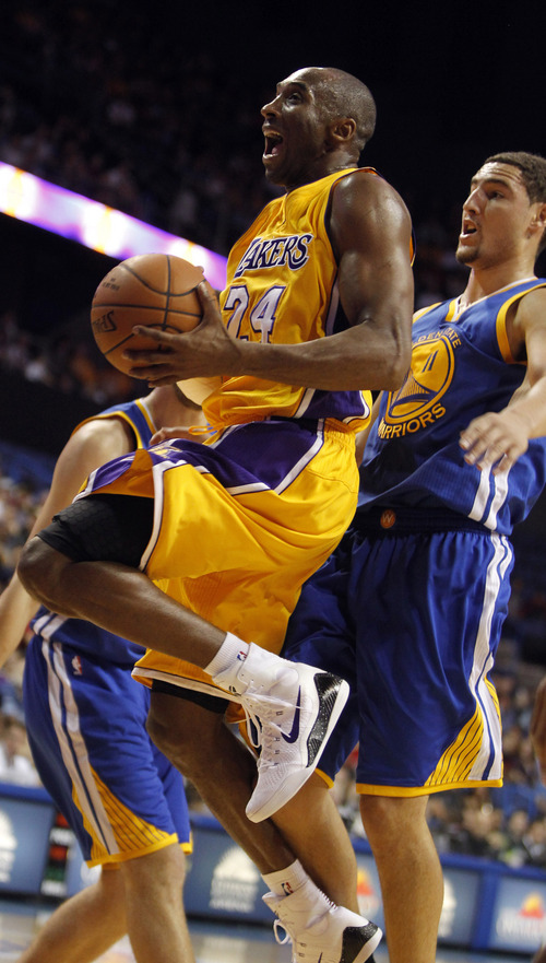 Los Angeles Lakers guard Kobe Bryant (24) leaps to the basket with Golden State Warriors guard Klay Thompson, right, defending during the first half of a preseason NBA basketball game, Sunday, Oct. 12, 2014, in Ontario, Calif. (AP Photo/Alex Gallardo)