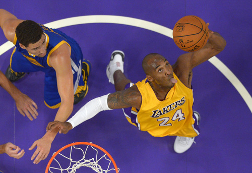 Los Angeles Lakers guard Kobe Bryant, right, grabs a rebound as Golden State Warriors guard Klay Thompson looks on during the first half of a preseason basketball game, Thursday, Oct. 9, 2014, in Los Angeles.  (AP Photo/Mark J. Terrill)