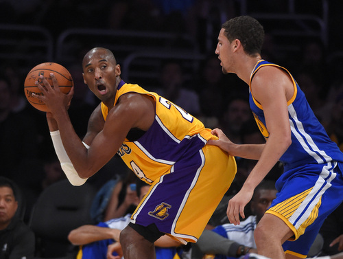 Los Angeles Lakers guard Kobe Bryant, left, backs in toward the basket as Golden State Warriors guard Klay Thompson defends during the second half of a preseason basketball game, Thursday, Oct. 9, 2014, in Los Angeles.  (AP Photo/Mark J. Terrill)