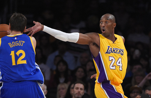 Golden State Warriors center Andrew Bogut, left, of Australia, heads for the basket as Los Angeles Lakers guard Kobe Bryant defends during the first half of a preseason basketball game, Thursday, Oct. 9, 2014, in Los Angeles.  (AP Photo/Mark J. Terrill)