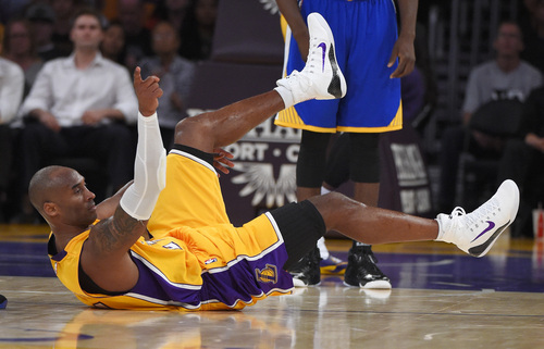 Los Angeles Lakers guard Kobe Bryant gestures after tripping during the first half of a preseason basketball game against the Golden State Warriors, Thursday, Oct. 9, 2014, in Los Angeles.  (AP Photo/Mark J. Terrill)