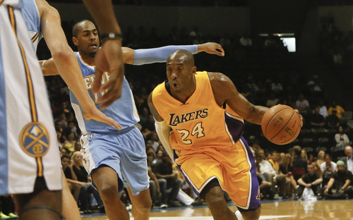 Los Angeles Lakers guard Kobe Bryant sails past Denver Nuggets guard Arron Afflalo while driving the lane during the first half of an NBA preseason basketball game  Monday, Oct. 6, 2014, in San Diego. (AP Photo/Lenny Ignelzi)