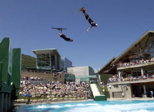 Members of the Flying Ace All-Stars Freestyle Aerial team take jumps into the landing pool as crowd watches at the Utah Olympic Park and Joe Quinney Winter Sportsw Center Friday.   Hartmann/photo  7/6/02