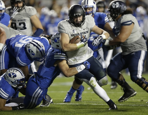 Utah State's Nick Vigil (41) carries the ball as he is tackled by BYU linebacker Alani Fua, left, in the first quarter during an NCAA college football game Friday, Oct. 3, 2014, in Provo, Utah. (AP Photo/Rick Bowmer)