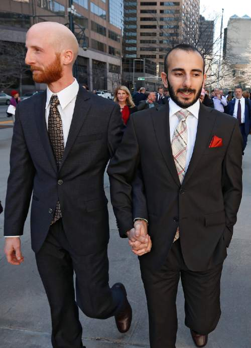 Plaintiffs challenging Utah's gay marriage ban Moudi Sbeity, right, and his partner Derek Kitchen, hold hands as they leave the courthouse following a hearing at the U.S. Circuit Court of Appeals in Denver, Thursday, April 10, 2014. The court is to decide if it agrees with a federal judge in Utah who in mid-December overturned a 2004 voter-passed gay marriage ban, saying it violates gay and lesbian couples' rights to due process and equal protection under the 14th Amendment. (AP Photo/Brennan Linsley)