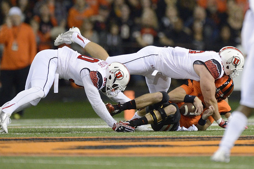 Oregon State quarterback Sean Mannion (4) is sacked by Utah defenders Hunter Dimick (49) and Pita Taumoepenu (50) during the first half of an NCAA college football game in Corvallis, Ore., Thursday, Oct.. 16, 2014. (AP Photo/Troy Wayrynen)