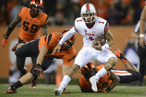 Utah quarterback Kendal Thompson (1) breaks away from Oregon State defenders for a 15-yard run and a first down during the first quarter of an NCAA college football game in Corvallis, Ore., Thursday, Oct. 16, 2014. (AP Photo/Troy Wayrynen)