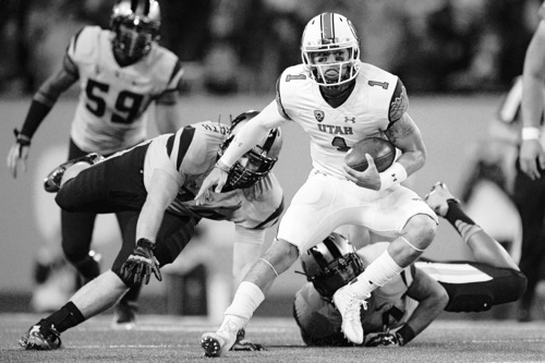 Utah quarterback Kendal Thompson (1) breaks away from Oregon State defenders for a 15-yard run and a first down during the first quarter in an NCAA college football game in Corvallis, Ore., Thursday, Oct. 16, 2014. (AP Photo/Troy Wayrynen)