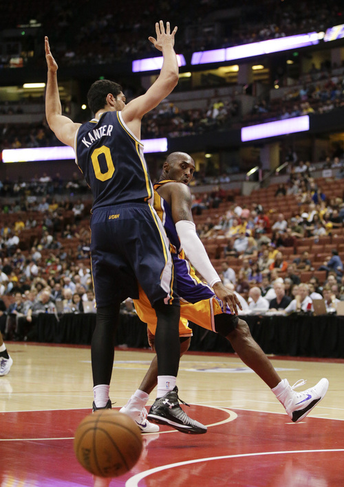 Los Angeles Lakers' Kobe Bryant, right, passes the ball around Utah Jazz's Enes Kanter during the second half of a preseason NBA basketball game Thursday, Oct. 16, 2014, in Anaheim, Calif. The Jazz won 119-86. (AP Photo/Jae C. Hong)