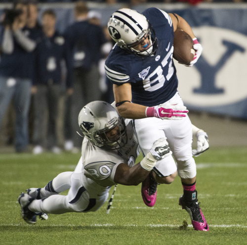 Rick Egan  |  The Salt Lake Tribune  Brigham Young Cougars wide receiver Mitchell Juergens (87) drags  Nevada Wolf Pack defensive back as he runs with teh ball, in football action, BYU vs The Nevada Wolf Pack at Lavell Edwards Stadium, Saturday, October18, 2014