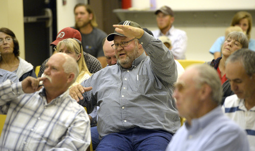 Al Hartmann  |  The Salt Lake Tribune Alan Johnson, a rancher with grazing lease land in western Juab County on the edge of the Utah Test and Training Range, asks questions of a U.S. Air Force representative at a public forum Monday Oct. 20, 2014, at West Desert High School in Partoun to discuss expanding the Utah Test and Training Range. He was concerned about losing his grazing land rights in an expansion of the training range.