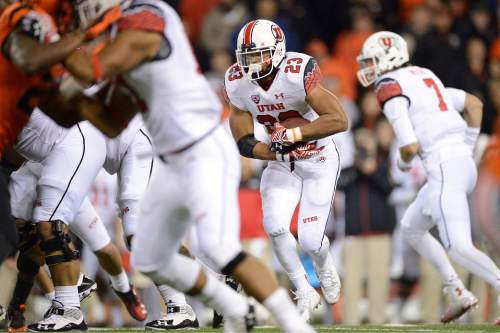 University of Utah running back Devontae Booker (23) takes a hand off up the field for a game winning touchdown against Oregon State during an NCAA college football game in Corvallis, Ore., Thursday, Oct.. 16, 2014. The University of Utah beat Oregon State 29-23 in overtime. (AP Photo/Troy Wayrynen)