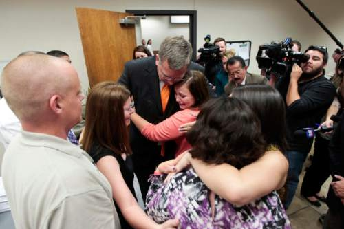 Spenser Heaps  |  Pool   Utah County prosecutor Craig Johnson embraces Heidy Truman's sister Amanda Wagner, as her brother-in-law, Jason Keller, left, sister Sommer Keller, second from left, mother Janet Wagner, second from right, and other family members react after the jury returned guilty verdicts in Conrad Truman's trial at 4th District Court in Provo on Wednesday, Oct. 22, 2014. Truman was found guilty of murder and obstruction of justice in the 2012 shooting death of his wife Heidy Truman.