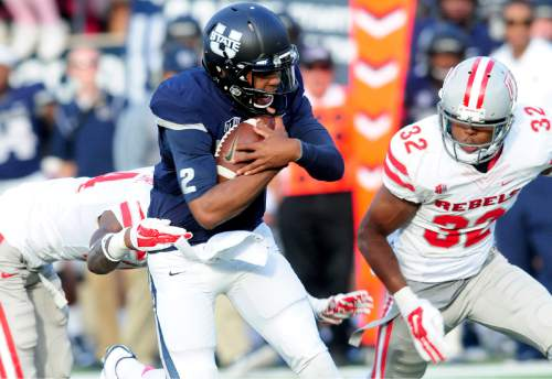 Utah State's quarterback Kent Myers (2) is tackled by UNLV's Kenny Keys during an NCAA college football game, Saturday, Oct. 25, 2014, in Logan, Utah. (AP Photo/The Herald Journal, John Zsiray)